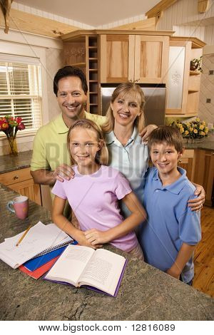 Caucasian family of four standing in kitchen posing with homework on counter.