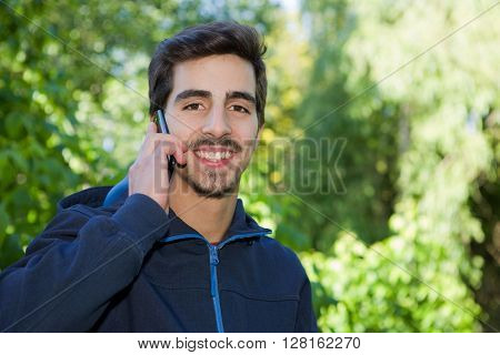 happy young casual man on the phone outdoor