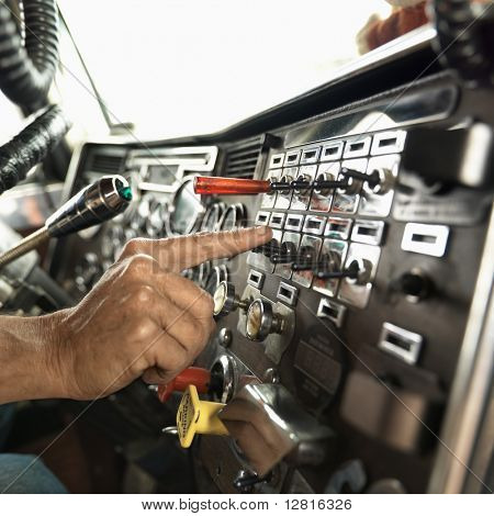 Interior of mid-adult Caucasian male hand pressing switch on dashboard of a tractor trailer.
