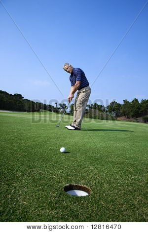 Caucasion mid-adult man putting golf ball with hole in foreground.