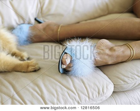 Feet shot of Caucasion middle-aged woman wearing furry heels beside dog paws both lying on couch.
