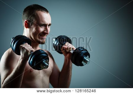 Close up of young man lifting weights over grey background (color toned image)