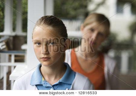 Niña preadolescente Caucásica con madre detrás de su mirar por encima del hombro.