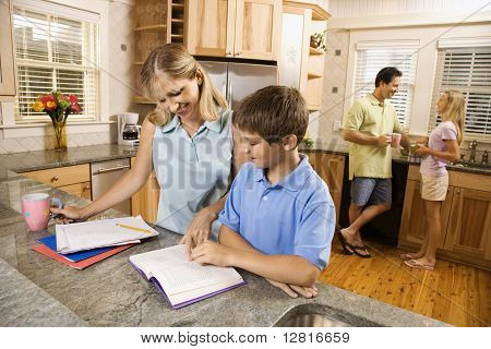 Caucasian family in kitchen doing homework and chatting.
