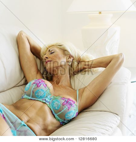 Tan Caucasion blonde middle-aged woman seductively lying in underwear on couch with arms raised.