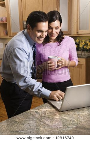 MId-adult couple looking at laptop computer while drinking coffee in kitchen.