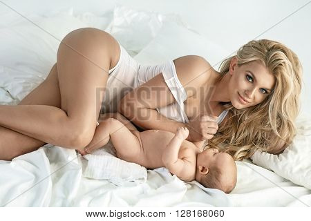 Blonde mom with newborn baby playing in bed