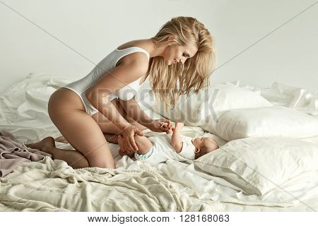Portrait of young blonde mother with newborn baby in bed