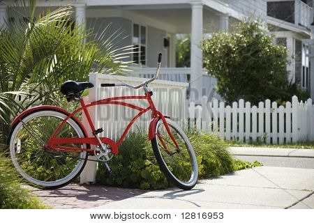 Red beach cruiser bicycle propped against fence in front of house.