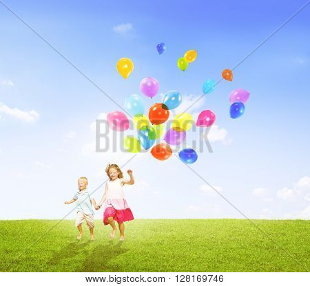 Little Girl and Boy Outdoors Holding Balloons