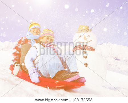 Siblings playing snow sledge in the snow.