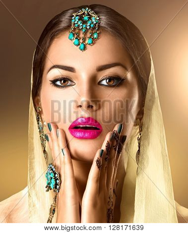 Beauty Indian woman portrait. Brunette Hindu model girl with brown eyes, mehndi or mehendi tattoo on her hand and national Indian jewels looking in camera. Indian girl in sari.