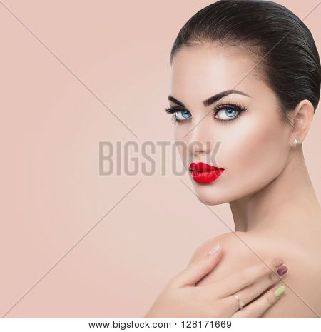 Beauty Fashion Model Woman face. Portrait with Red sexy lips and blue eyes, perfect make up. Beautiful Brunette Woman with Luxury Makeup touching her soft skin shoulder. Skin care. Beige background