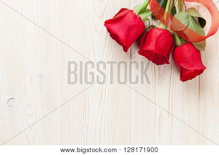 Red roses over wooden table. Valentines day background. Top view with copy space