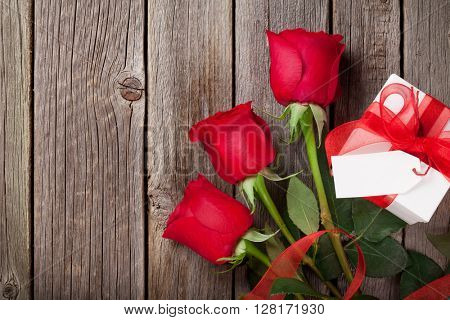 Red roses and gift box over wooden background. Top view with copy space