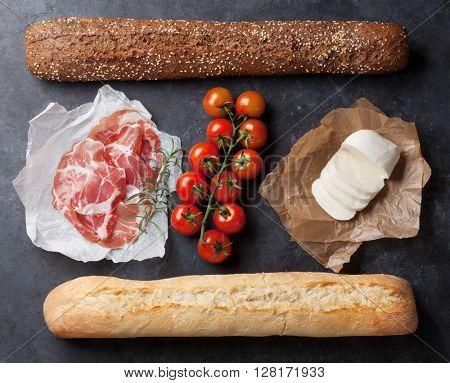 Ciabatta sandwich cooking with prosciutto and mozzarella cheese over stone background. Top view