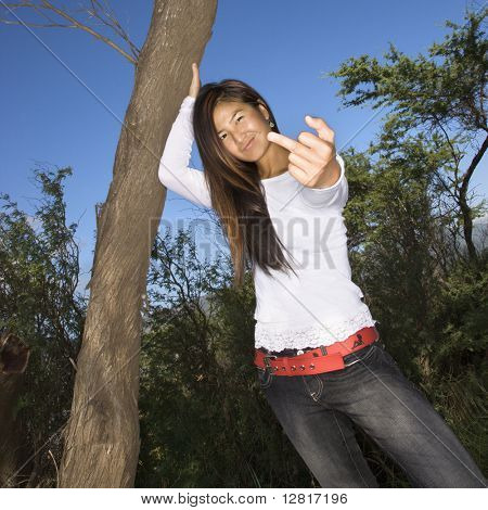 Young adult Asian female with one hand on tree and other hand  giving the viewer the middle finger.