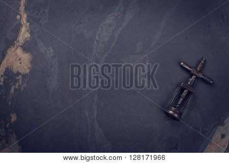 Vintage corkscrew on stone table. Top view with copy space. Toned