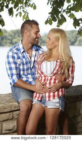 Happy casual romantic man embracing young blonde woman outdoors, smiling, looking at each other.