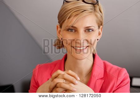Closeup portrait of attractive young blonde businesswoman, smiling, looking at camera.