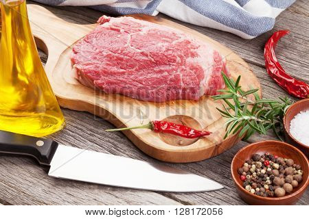 Raw beef steak with spices and herbs on wooden table