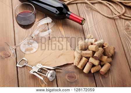 Glass of red wine, bottle and corkscrew on rustic wooden table. Top view with copy space