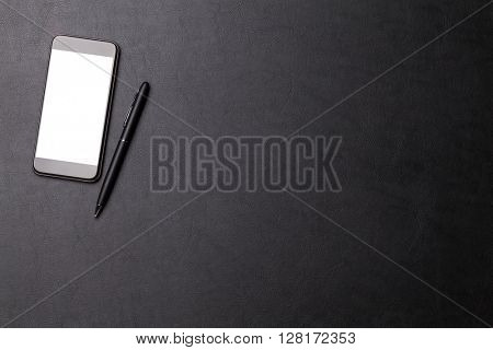 Office leather desk table with smartphone and pen. Top view with copy space