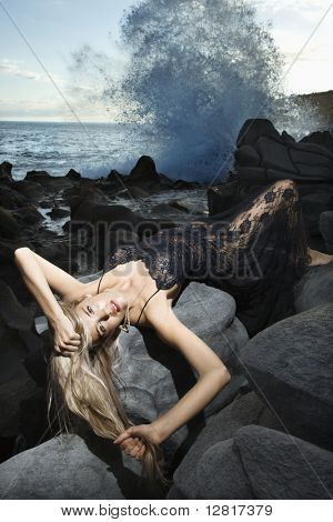 Portrait of Caucasian young adult woman lying on back on rocky coast with hair hanging down making eye contact.