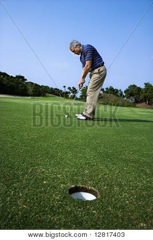 Image of mid-adult male putting golf ball with hole in foreground.