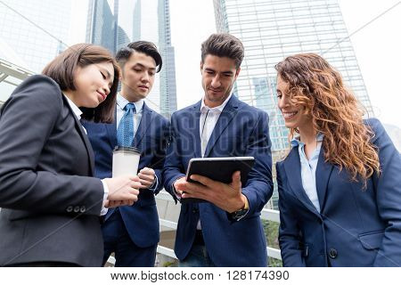 Business partners discuss something on tablet computer