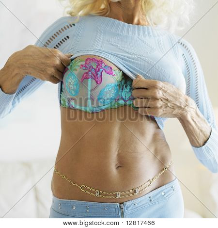 Tan Caucasion middle-aged woman seductively lifting her sweater exposing her midriff and breast.