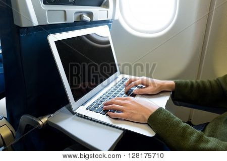 Woman using laptop computer on airplane