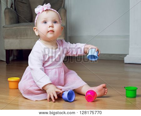 adorable baby playing at home on the floor with toys