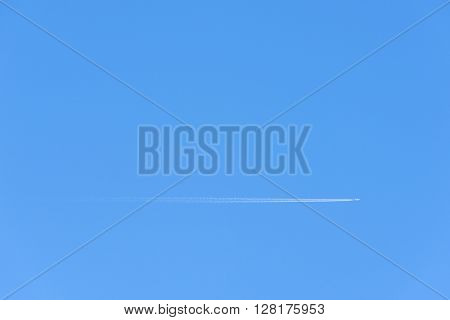 Airplane and its contrails in a clear blue sky