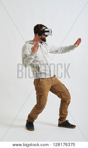 A young man in casual clothes and virtual reality glasses is fighting in 3d reality