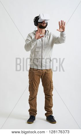 A young bearded man in casual clothes, headphones and virtual reality glasses is trying to touch something in front of him
