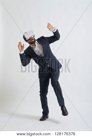 Businessman in a formal wear and virtual reality glasses scaring something