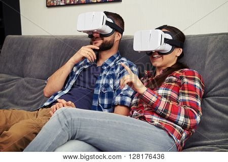 A young man and woman in casual clothes and virtual reality glasses are very excited