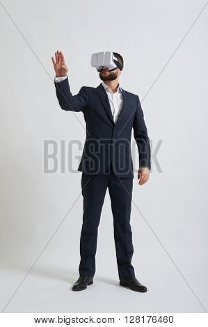 Businessman in a formal wear and virtual reality glasses is trying to touch something in front of him