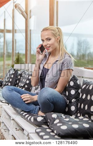 female enjoying recreation time while chatting with her mobile phone on terrace, smiling successful young woman read good news on the smart phone