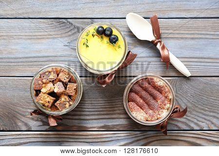 Assorted jar cakes on wooden table