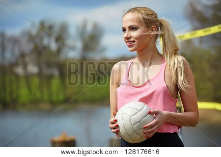 Joyful sexy blond girl playing volleyball outdoors on the lakeside