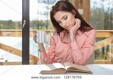 Charming woman sitting by wooden table and reading book