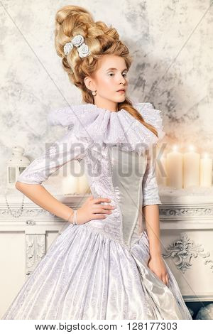 Elegant young woman in a lush white medieval dress with hair in the style of the Renaissance. Beautiful Ice Queen in her snow palace.
