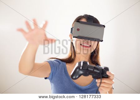 Woman looking though VR device with playing video game