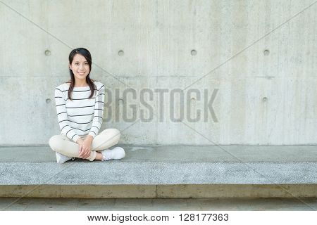 Young woman against concrete wall