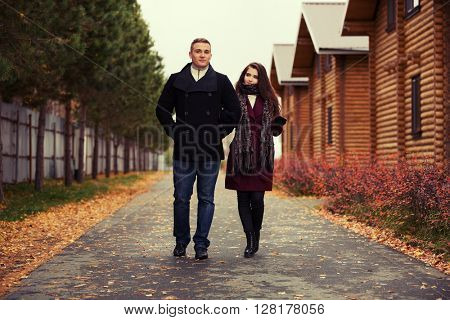 Young couple in love walking outdoor. Male and female fashion model next to log cottage