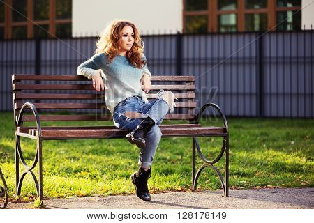 Happy young fashion woman with long curly hairs sitting on bench in city park. Female fashion model in ripped jeans