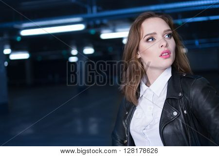 woman in car garage  looking on the side , car dealer or driver