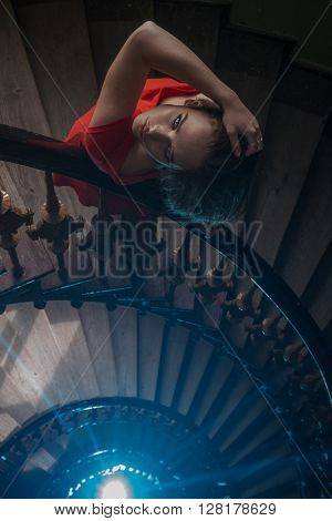 pretty woman in red dress on the old stairs